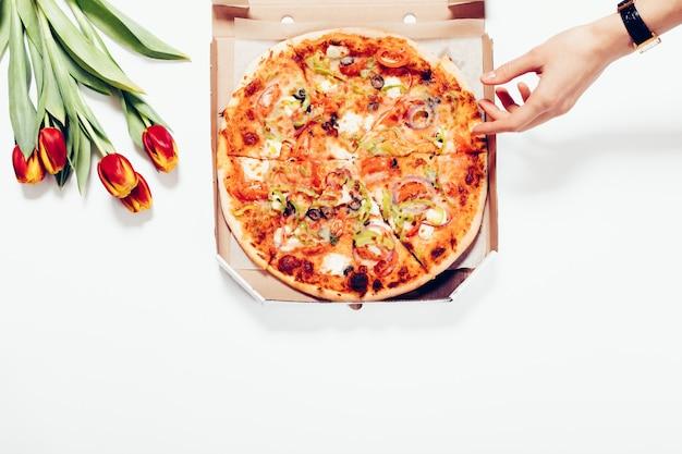 Vista superior de una pizza en una caja, tulipanes y una mano femenina sobre un fondo blanco.