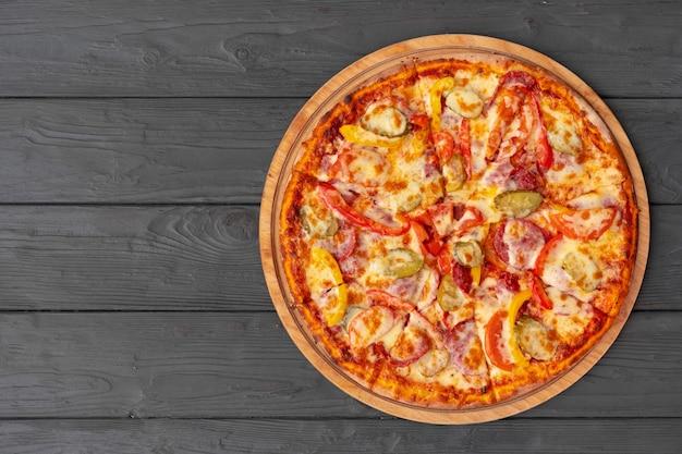 Vista superior de pizza caliente en mesa de madera negra