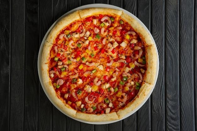 Vista superior de pizza con camarones y filete de pollo.
