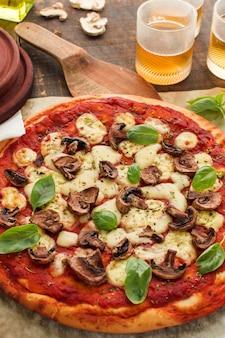 Vista superior de pizza casera con champiñones; albahaca y queso en mesa de madera