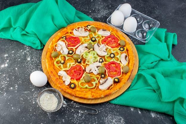 Vista superior de la pizza de champiñones con tomates, aceitunas, champiñones, todos en rodajas por dentro con harina sobre el fondo gris, masa de pizza de tejido verde italia