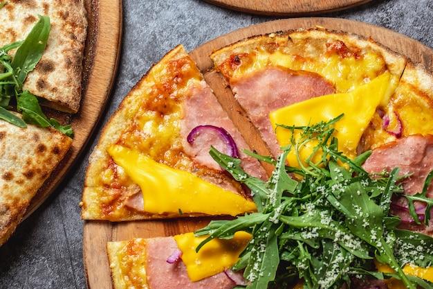 Vista superior pizza de jamón y queso con queso derretido parmesana y rúcula en un tablero
