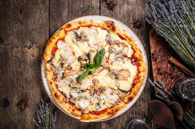 Vista superior de la pizza de masa esponjosa recién horneada italiana con champiñones en la mesa de madera