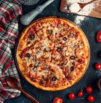 Vista superior de pizza mixta con tomate, aceituna negra y queso fundido