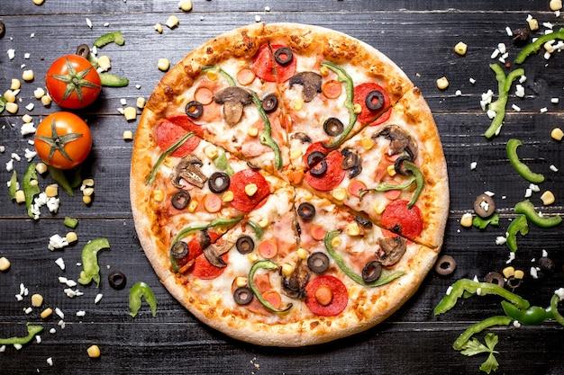 Vista superior de pizza de pepperoni con salchichas de champiñones pimiento verde oliva y maíz en madera negra