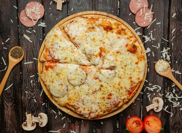 Vista superior de pizza de pepperoni con salchichas, salsa de tomate, queso y chispas de hierbas