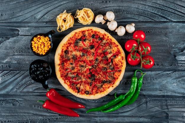 Vista superior pizza con tomates, espaguetis, pimientos, aceitunas, champiñones y maíz sobre fondo de madera oscura. horizontal