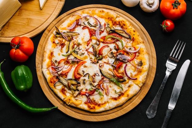 Vista superior de pizza vegetariana con berenjena, pimiento, cebolla roja, tomate y champiñones