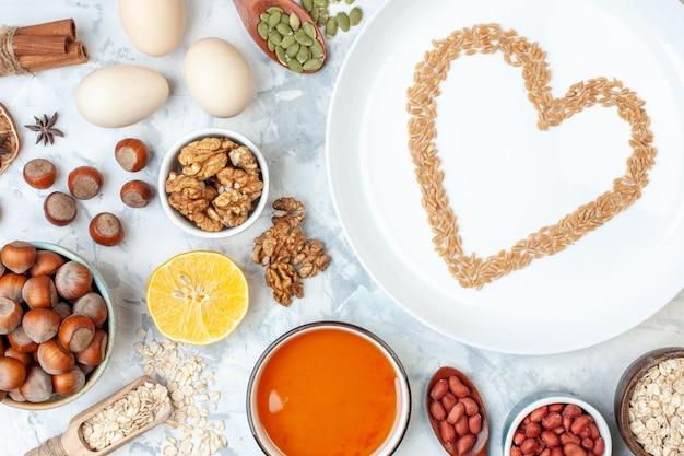 Vista superior placa blanca con gelatina huevos diferentes nueces y semillas en masa blanca pastel de color pastel de azúcar dulce corazón de nuez