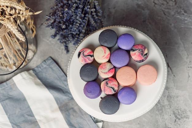 Vista superior de la placa blanca con macarons de colores en la mesa de mármol con una servilleta y lavanda. sabroso postre