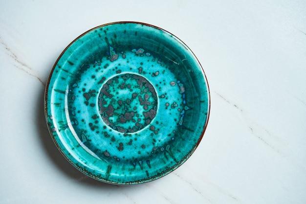 Vista superior en placa de cerámica azul vacía hecha a mano sobre una superficie de mármol gris. copiar espacio para texto. utensilios de cocina con estilo