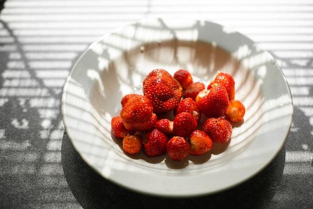 Vista superior de una placa de cerámica llena de fresas orgánicas frescas y dulces recogidas en el jardín a la luz del sol. cortina de ventana en la mesa de la cocina.