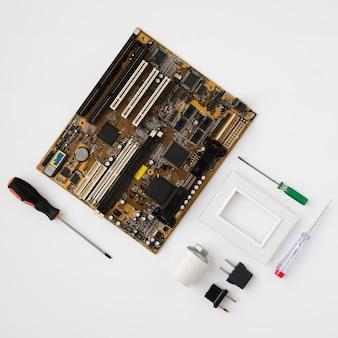 Vista superior de la placa de circuito y equipo eléctrico en superficie blanca