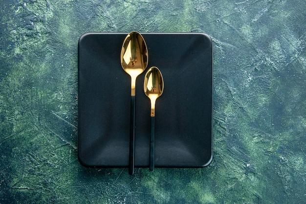 Vista superior de la placa cuadrada negra con cucharas de oro sobre fondo azul oscuro, restaurante, cena, cubiertos, comida, color, utencil