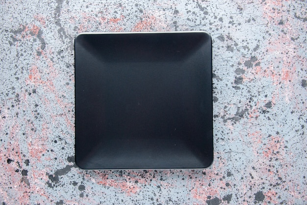 Vista superior placa cuadrada negra sobre fondo claro servicio cubiertos cena bandeja de comida mesa de color restaurante