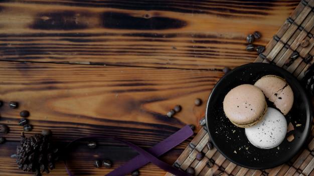 Vista superior de la placa negra de macarons de café en la mesa rústica de bambú maton