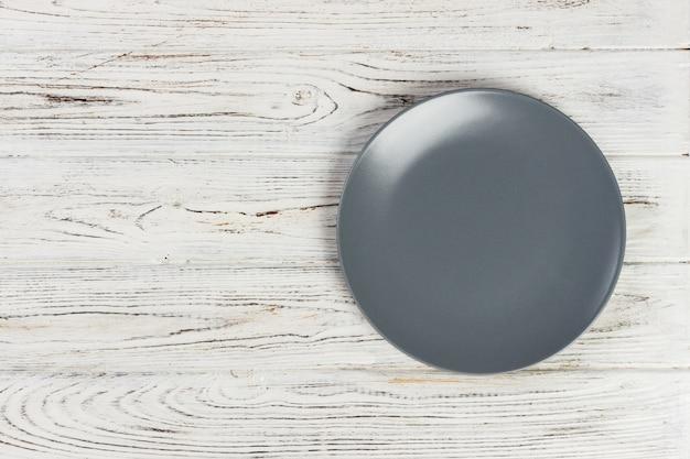 Vista superior placa redonda vacía en la mesa de madera rústica blanca con espacio de copia