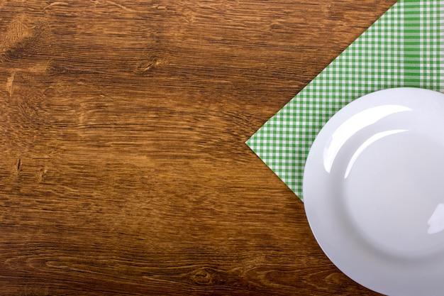 Vista superior de la placa vacía limpia sobre fondo de mesa de madera