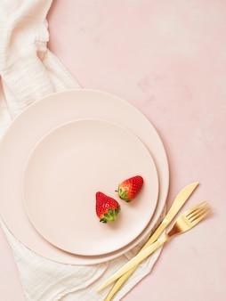 Vista superior de las placas de cerámica con fresas y cubiertos de oro sobre fondo rosa pastel