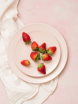 Vista superior de las placas de cerámica con fresas sobre fondo rosa pastel