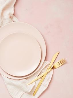 Vista superior de las placas de cerámica vacías y cubiertos de oro sobre fondo rosa pastel