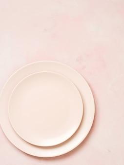 Vista superior de las placas de cerámica vacías sobre fondo rosa pastel