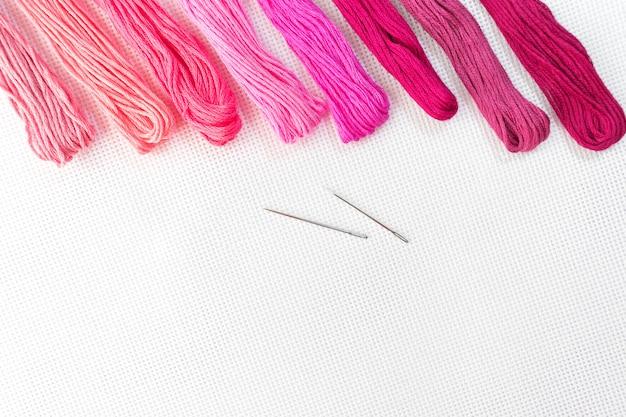 Vista superior plana con bordado lienzo, agujas, hilos en colores rojos.