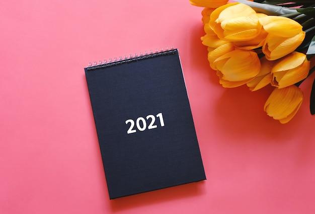 Vista superior plana laicos del diario negro o planificador 2021 con flor de tulipán amarillo sobre fondo rojo con espacio de copia, concepto de resoluciones de año nuevo