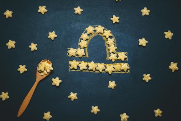 Vista superior plana libra, signo del horóscopo hecho de crujientes estrellas de maíz en un negro