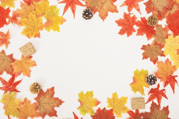 Vista superior plana pone coloridas hojas de arce, conos, hermosas cajas de regalo en blanco