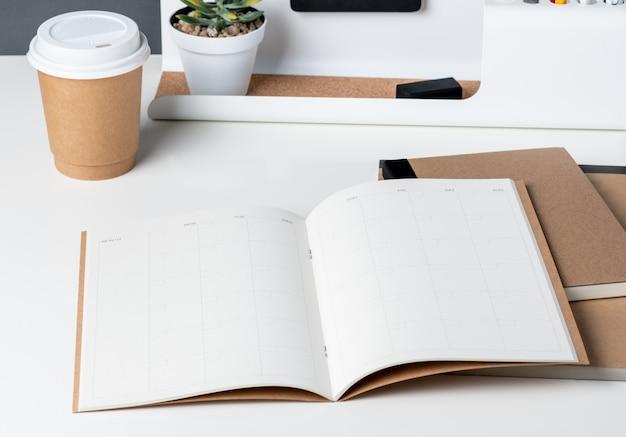 Vista superior del planificador de calendario abierto con papelería de oficina moderna