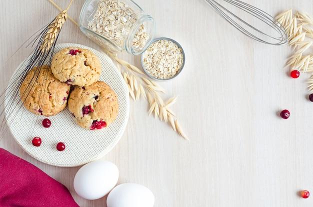 Vista superior, plano, cocinando galletas de avena con ingredientes, arándanos y cereales, sobre fondo de madera clara, espacio de copia