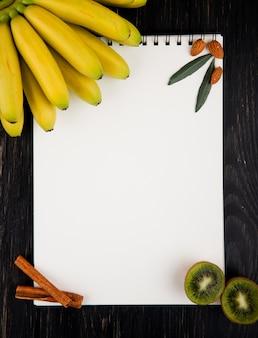Vista superior de plátanos frescos y kiwis con un cuaderno de dibujo, palitos de almendras y canela en negro
