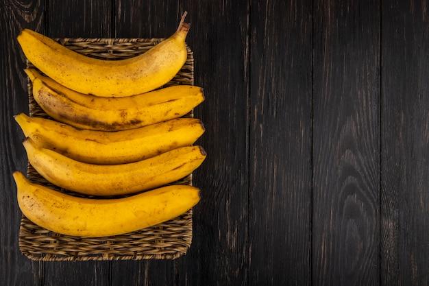 Vista superior de plátanos maduros en una cesta de mimbre en madera con espacio de copia