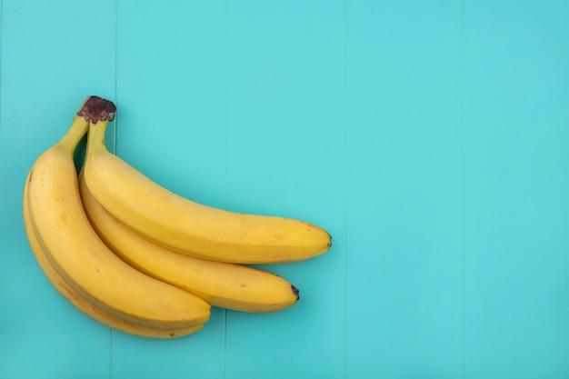 Vista superior de plátanos sobre una superficie turquesa