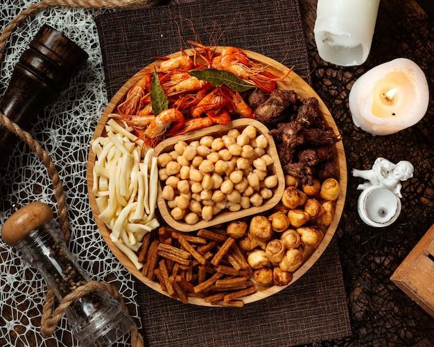 Vista superior de un plato de aperitivos de cerveza redonda con garbanzos de camarones y queso de cadena