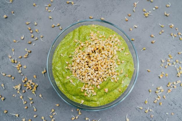 Vista superior del plato de batido verde en un tazón con brotes de trigo sarraceno verde. desayuno saludable. plato vegetariano. comida llena de vitaminas. super bowl