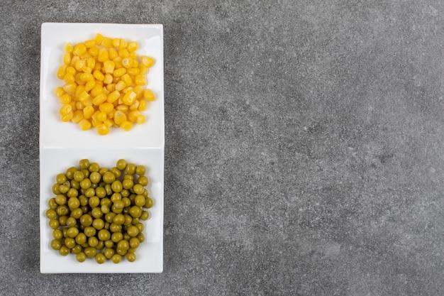 Vista superior del plato blanco lleno de maíz y guisantes enlatados