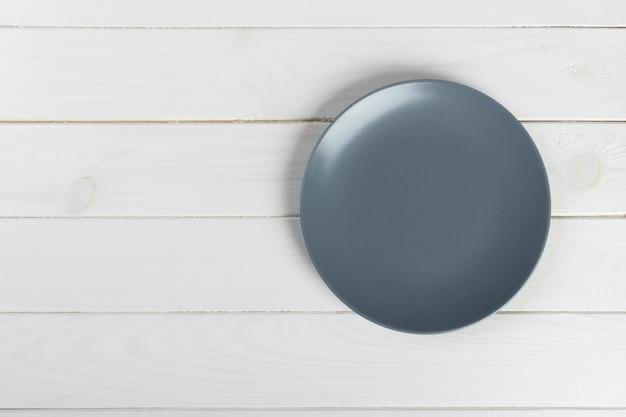 Vista superior del plato en blanco sobre un fondo de madera con espacio de copia