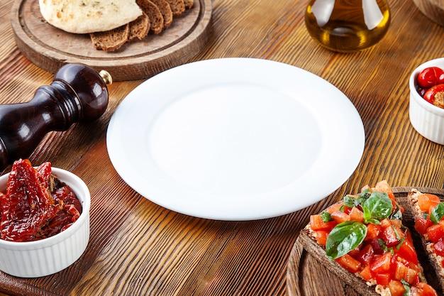 Vista superior plato blanco vacío para comida. placa en blanco para servir alimentos en composición con tomates secados al sol, bruschetta y utensilios sobre fondo de madera. lay flat