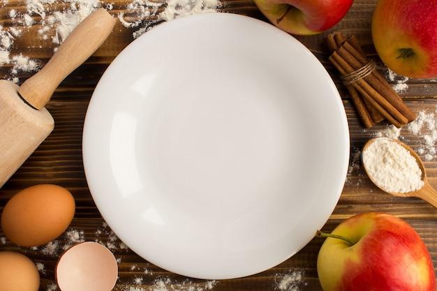 Vista superior del plato blanco vacío e ingredientes para hornear tarta de manzana en la mesa de madera