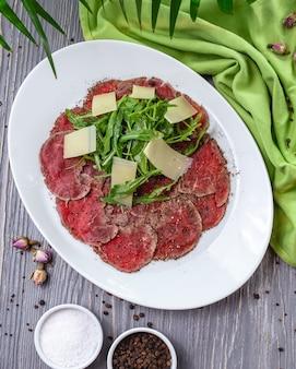 Vista superior plato de carne basturma con rúcula y queso parmesano