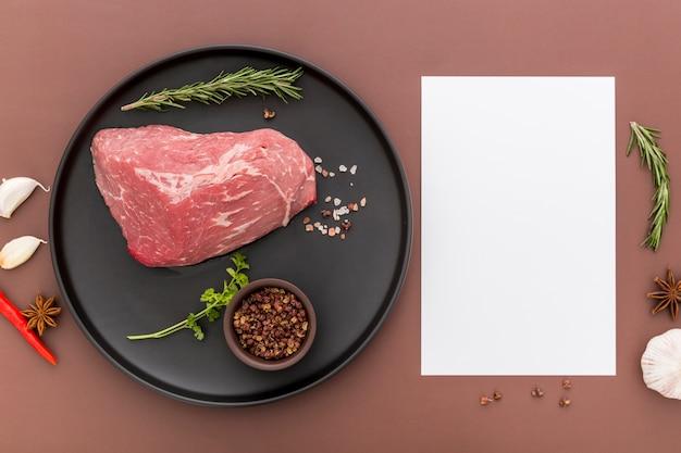 Vista superior del plato con carne y papel de menú en blanco