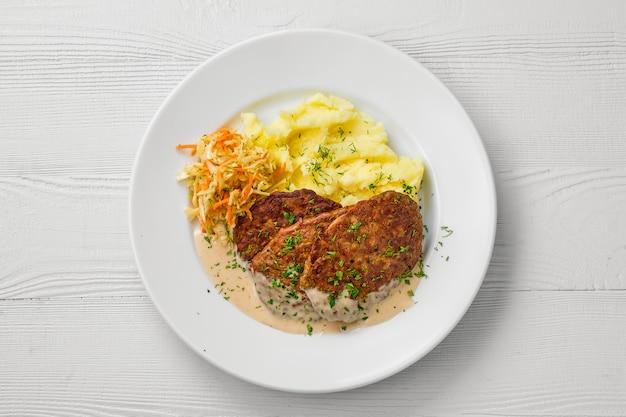 Vista superior del plato con chuleta de hígado, puré de papas y repollo en vinagre