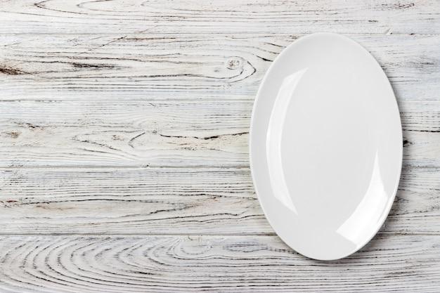 Vista superior del plato de comida blanca vacía sobre un fondo de madera