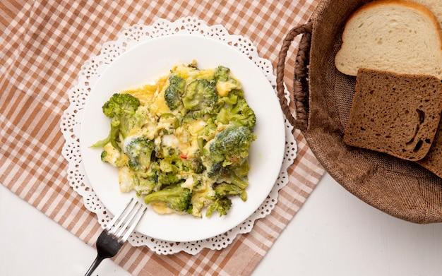 Vista superior del plato de comida con brócoli y huevos con un tenedor sobre tela y panes en rodajas sobre fondo blanco.