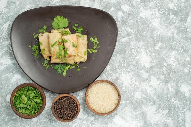 Vista superior del plato de comida de repollo relleno y platos de arroz papper negro y hierbas en el lado izquierdo de la mesa