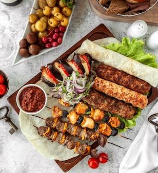 Vista superior del plato de kebab en brochetas servidas con ensalada