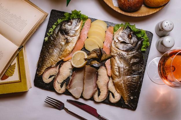 Vista superior plato de pescado con patatas y una rodaja de limón con una copa de vino