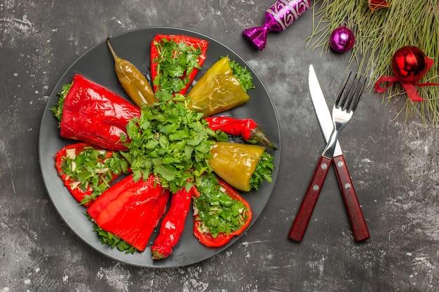 Vista superior del plato pimientos con hierbas cuchillo tenedor juguetes para árboles de navidad